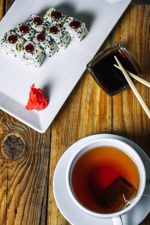 Plate of sushi and cup of tea on wood background