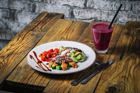 Plate of salmon salad and glass of berry smoothies on wood background 写真素材