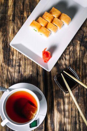 Philadelphia roll sushi and cup of tea on wood background. Sushi menu. Japanese food.