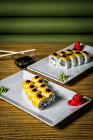 Two plates of sushi on the table in front of green blind 写真素材