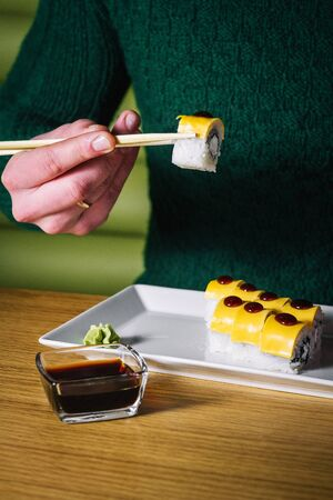 Mens hands hold sushi with chopsticks