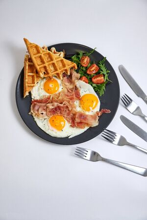 Hearty breakfast of scrambled eggs with bacon, waffles,  salad of greens and tomatoes on black plate