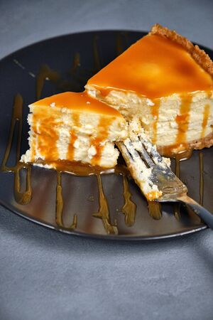 Sweet dessert from air curd cheesecake poured with caramel on a dark background