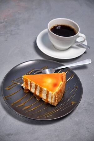 Dessert from air curd cheesecake poured with caramel with a cup of invigorating coffee on a dark background