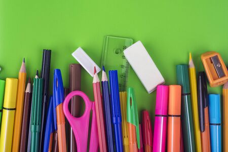 On a green background colored pencils and pens, office stationery Reklamní fotografie