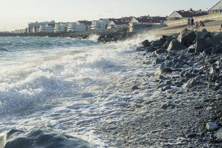 Big waves on the rocky shore near the hotel Stock Photo