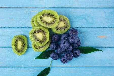 Fresh blueberries and kiwi slices on a wooden blue background, with green leaves