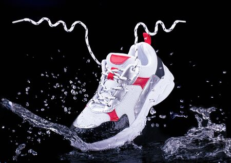 Sports sneakers on a black isolated background in splashes of water, floating laces in the air 版權商用圖片