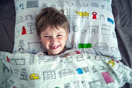 A cute boy is lying on the bed. A 7-year-old boy is playing on the bed. Happy child. Rest. Sleep. Morning. Reklamní fotografie