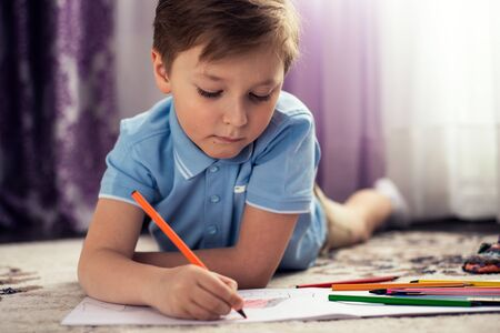 A happy child draws with pencils, lying on the floor of the house. Childrens leisure. Family and children.