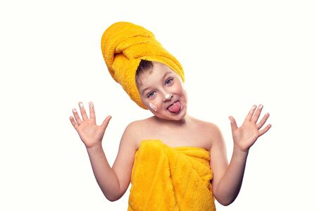 A boy without one tooth with cream on his face and in a towel