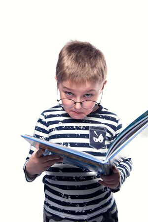 Portrait of a cute boy with glasses holding a book on a white background