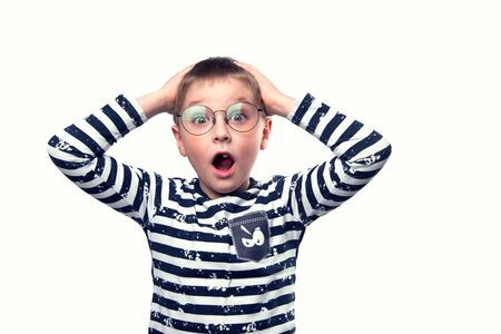A surprised boy with glasses holds his head against a white isolated background Reklamní fotografie