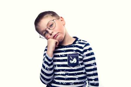 A tired boy with glasses rests his cheek against a white isolated background