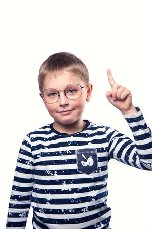A smart boy with glasses held up a finger against a white isolated background