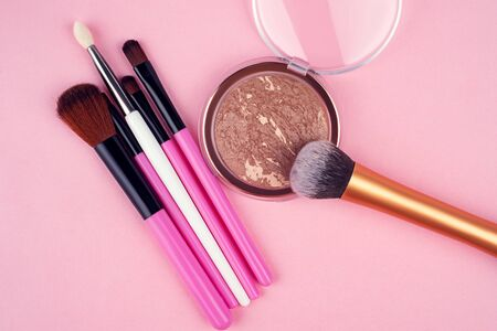 Decorative cosmetics, set of cosmetics on a pink background top view