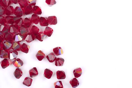 Precious stones of red color are scattered on a white background isolated
