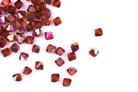 Precious stones of red color are scattered on a white background