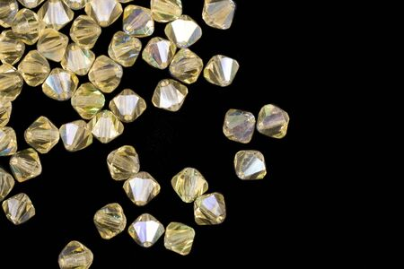 Yellow gemstones are scattered on a black background isolated