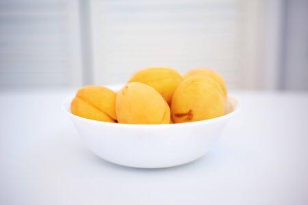 Apricot on a wooden white background. Sliced apricot, apricots in a plate Reklamní fotografie