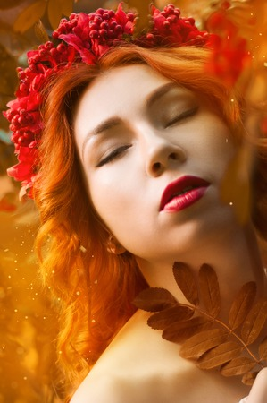 acorn tree: Colorful autumn portrait of beautiful red head model with rowan berries