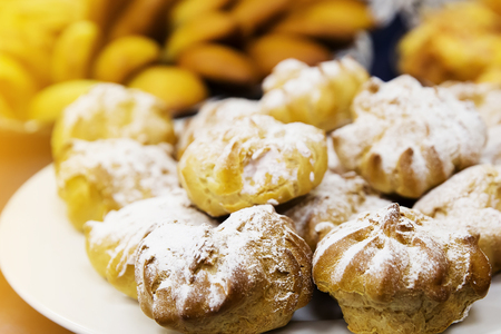 creampuff: Cream puffs filled with pastry cream and sprinkled with powdered sugar catering on blue table