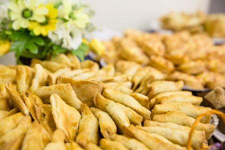Small pies lie on a plate with basket of flowers on a blue table