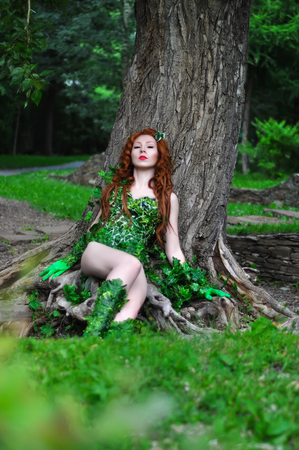 Young beautiful red-haired girl in the image of the comic book poison ivy is surrounded by greenery in the woods