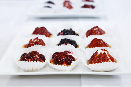Catering sweet fruit and berry tarts dessert tray assorted on white table Stock Photo