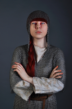 Medieval girl in chain mail with red hair stands on a gray background with blood on her hands. Studio shot Stock fotó