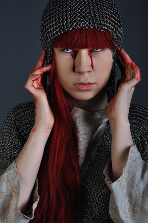 Medieval girl in chain mail with red hair stands on a gray background with blood on her hands. Studio shot Stock Photo