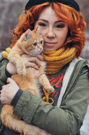 Portrait of a red-haired girl with a red cat outdoor on the street