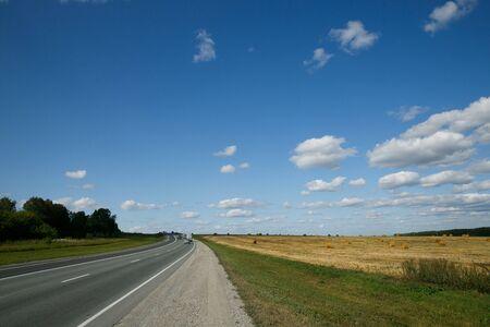 Ruta interurbana pasando campos y bosques en un día de verano con cielo nublado