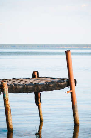 Old wooden pier on the sea on a summer evening at sunset