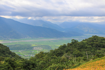 Taiwan Hualien beautiful scenery of daylily flowers with village and mountains in a sunny day Stock Photo - 86039260