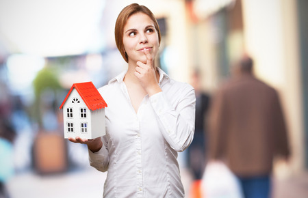 a small house: blond woman with a small house thinking Stock Photo