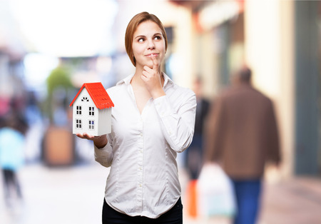 sold small: blond woman with a small house thinking Stock Photo
