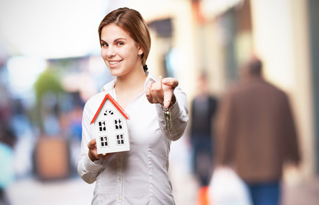 sold small: blond woman with a small house Stock Photo