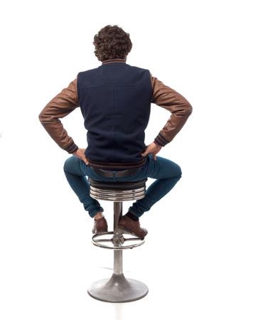 posterior del hombre joven con el taburete de la barra Foto de archivo