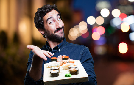 humourous: young man eating sushi. show sign