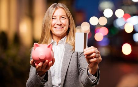 senior beautiful woman with piggy bank