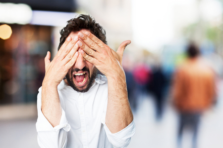 young funny man covering eyes Stock Photo