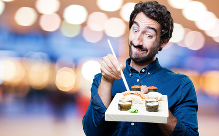young man eating sushi. show sign