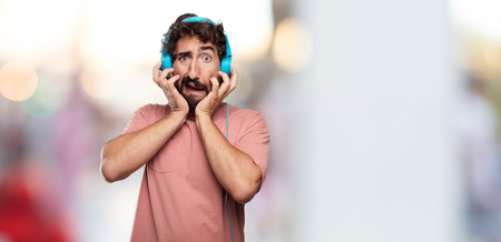 young bearded man with a stressed gesture, with both hands clenched half covering face. Imagens