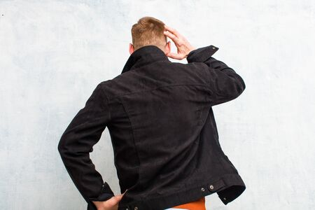 young red head man feeling clueless and confused, thinking a solution, with hand on hip and other on head, rear view against grunge wall