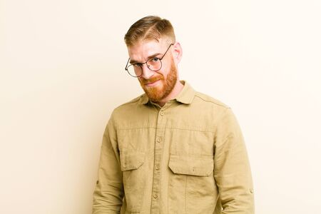 young red head man looking proud, confident, cool, cheeky and arrogant, smiling, feeling successful against beige background Standard-Bild