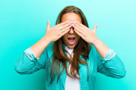 young woman smiling and feeling happy, covering eyes with both hands and waiting for unbelievable surprise against blue background