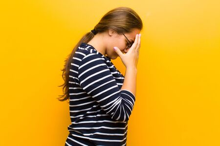 young pretty woman covering eyes with hands with a sad, frustrated look of despair, crying, side view against orange background