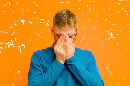 young red head man feeling sad, frustrated, nervous and depressed, covering face with both hands, crying against grunge orange wall
