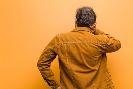 young handsome man thinking or doubting, scratching head, feeling puzzled and confused, back or rear view against orange wall